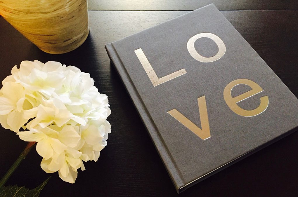 A NY Madison Couture Book with LOVE stamping next to flowers and vase