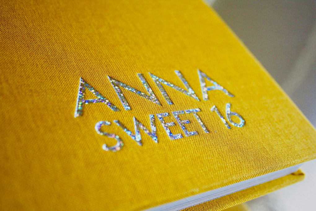A Couture Book with yellow linen cover stamped with holographic foil.